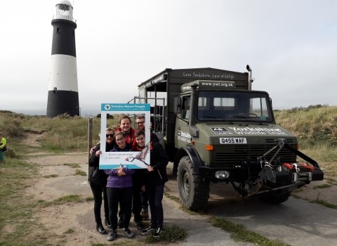 Volunteers from Yorkshire Wildlife Trust stood in front of Spurn lighthouse with the Unimog vehicle