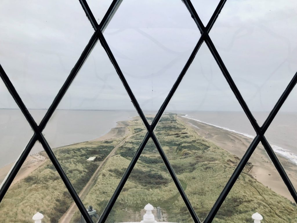 A view from the top of Spurn Point lighthouse looking out to the end of the narrow spit of land with the sea and the Humber Estuary either side