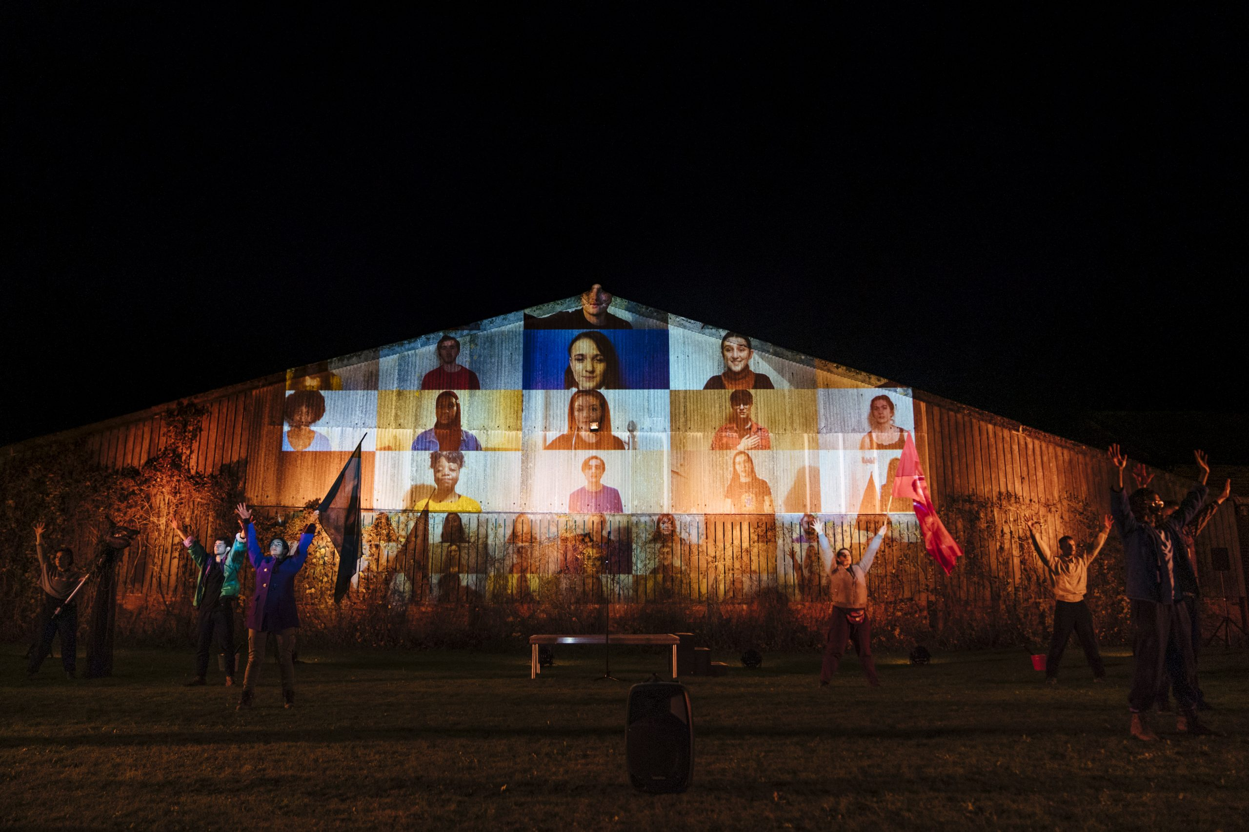 Projections of various National Youth Theatre cast members on the side of a building as part of the University of Hull co-production of The Last Harvest